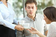 Disloyal boyfriend looking at breast of a waiter. In front of his distracted girlfriend stock photography