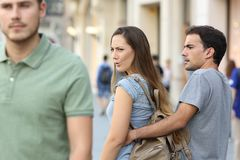Disloyal woman looking another man and her angry boyfriend. Disloyal women looking another men and her angry boyfriend looking at her on the street Stock Photos