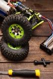 Dismantled broken Rc crawler model toy repair. Dismantled broken Rc radio control car crawler model toy repair. Green toy suv in repairshop workplace, closeup Stock Image