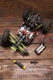 Dismantled broken Rc crawler model toy repair. Dismantled broken Rc radio control car crawler model toy repair. Green toy suv in repairshop workplace, top view Stock Images