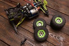 Dismantled broken Rc crawler model toy repair. Dismantled broken Rc radio control car crawler model toy repair. Green toy suv in repairshop workplace, top view Royalty Free Stock Images
