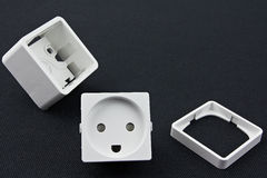 Dismantled electrical outlet. Lying on a black surface stock images