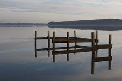Dismantled Jetty. Dismantled wooden jetty rerlected in the water on a frosty day Royalty Free Stock Photos