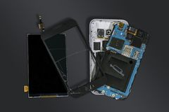 Dismantled mobile phone with broken display screen isolated on d. Ark grey background royalty free stock image