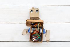 Dismantled robot with hands on white wooden background. flat lay Royalty Free Stock Images