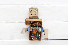 Dismantled robot with hands on white wooden background. flat lay Stock Photo