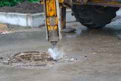 Dismantling of asphalt concrete pavement with pneumatic jackhammer during road works. Dismantling of asphalt concrete pavement with pneumatic jackhammer during stock photography