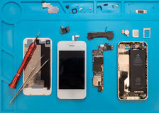 Dismantling the broken smartphone for repair. Flat lay image of dismantling the broken smart phone for preparing to repair or replace some components, Top view Royalty Free Stock Photography