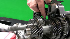 Dismantling car gearbox 4. Teacher showing parts. Hand of man is showing parts of a disassembled clean car gearbox on the table or trolley. Isolated on green stock video footage