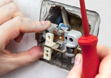 Dismantling and replacing an old, defective wall power switch light. Royalty Free Stock Photos
