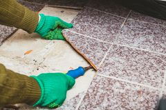 Hands take tile with chisel. Dismantling of tile. Hands in green working gloves undermine the broken tile with a chisel stock photo