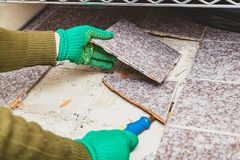 Hands take tile with chisel. Dismantling of tile. Hands in green working gloves undermine the broken tile with a chisel royalty free stock photos