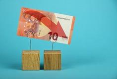Disminución euro de la moneda ilustrada sobre azul Fotografía de archivo libre de regalías