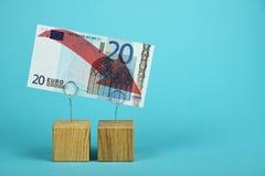Disminución euro de la moneda ilustrada sobre azul Imagenes de archivo