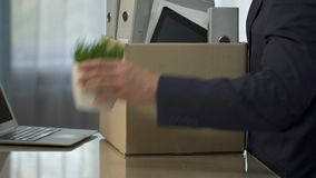 Dismissal, manager putting his personal things in box and leaving workplace