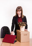 Dismissed girl in office with a box and flower closes laptop Royalty Free Stock Photo