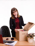 Dismissed girl in office near table collects personal belongings a box Royalty Free Stock Photos