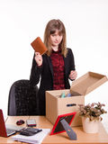 Dismissed girl office throws a notebook in box Royalty Free Stock Images