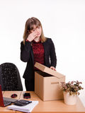 Dismissed girl in office wipes tears and collects things Royalty Free Stock Photos