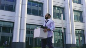A dismissed handsome man with a beard, a manager in formal attire, upset after being fired, goes along with a box of. Personal belongings. Close-up, depression stock footage