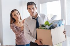Dismissed man carrying a heavy box while his wife comforting him. Unpleasant moment. Smart experienced men coming home with a box of personal items and looking Royalty Free Stock Photography