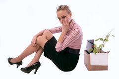The dismissed working woman with a box in grief. Sits on a floor Stock Images