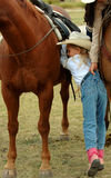 Dismount #2. Little cowgirl dismounting bay horse with adult assist stock image