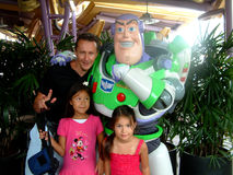 Disney Buzz lightyear. Hong Kong, Circa September 2010. Children and father posing with Disney Buzz Lightyear at the Hong Kong Disney resort Royalty Free Stock Photo