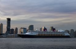 Disney Cruise ship coming into New York harbor. At sunset. New Jersey skyline in the background Stock Photography