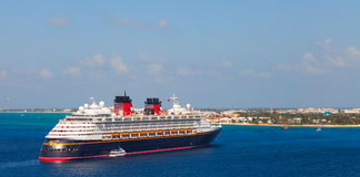 Disney Magic cruise ship was tendered next to the shore. Over 3,000 passengers came out to visit beautiful caribbean island. Stock Image