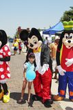 Disney Mickey Mouse, Goofy and Minnie Mouse with small girl at festival Stock Images
