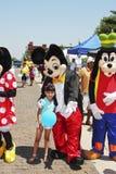Disney Mickey Mouse, torpe y Minnie Mouse con la pequeña muchacha en el festival Imagenes de archivo