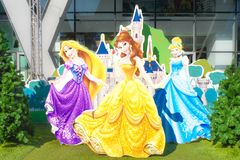 Disney Princesses Rapunzel, Belle, Cinderella and Disney castle behind them stock image