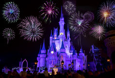 Disney`s Cinderella Castle With Fireworks. Disney`s Magic Kingdom Cinderella castle at night, lit in purple colors with fireworks stock photography