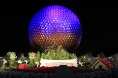 Disney`s EPCOT Center sphere illuminated at night during Holidays Season with Mickey Mouse, Minnie and Pluto characters grass scul. Ptures on the foreground Royalty Free Stock Photo