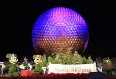 Disney`s EPCOT Center sphere illuminated at night during Holidays Season with Mickey Mouse, Minnie and Pluto characters grass scul. Ptures on the foreground, USA Stock Photo