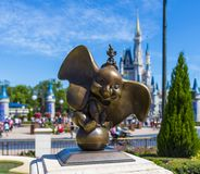 Disney World Orlando Florida Magic Kingdom Dumbo bronze statue. Dumbo statue at walt disney world magic kingdomorlando florida with Cinderella  Princess castle Royalty Free Stock Photos
