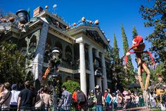 Disneyland Haunted House Halloween Theme. Disneyland decorated for Halloween. Crowds line up for the Haunted Mansion stock images