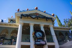 Disneyland Halloween Haunted House with Christmas Clock. Disneyland decorated for Halloween. Haunted Mansion decorated for October holiday with Christmas Count Stock Image