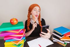 Disobedient redhead schoolgirl distracted on lesson and do selfie on white background. To be distracted from study. stock photos