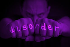 Disorder written on an angry man's fists. Disorder written on the fingers of an angry man's fists. Purple colored. Message concept image Royalty Free Stock Photo