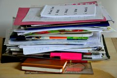 Disordered papers, clutter on a desk. Papers and notebooks in a mess on a working desk. Disorder, clutter, hoarding concept Royalty Free Stock Photo