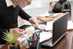 Disorganized businessman looking for documents royalty free stock photo