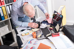 Disorganized businessman looking for documents. On his desk Royalty Free Stock Image