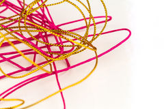Disorganized pile of pink and gold  rope. On white background Stock Image