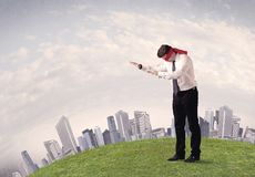 Disoriented blindfolded businessman concept. Young blindfolded businessman steps on a a patch of grass with a grey buildings in the background Stock Images