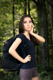 Disoriented Hiking Girl with Travel Backpack. Portrait of a young woman carrying a backpack and feeling lost Royalty Free Stock Image