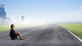She is in dispair and isolation. Bored young businesswoman sitting alone on asphalt road Stock Image