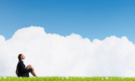 She is in dispair and isolation. Bored young businesswoman sitting alone on green grass Stock Photos