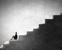 She is in dispair and isolation. Bored young businesswoman sitting alone on ladder steps Stock Photo